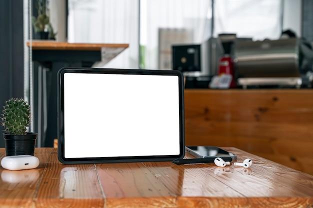 Tablet schermo bianco vuoto con gadget sulla tavola di legno nella caffetteria.