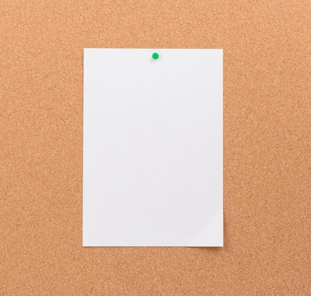 Foglio di carta bianco vuoto allegato con pulsante verde su sfondo marrone, copia dello spazio