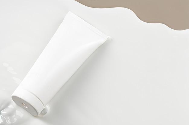 Tubo di prodotto per la cura della pelle bianco vuoto su sfondo beige con spazio di copia
