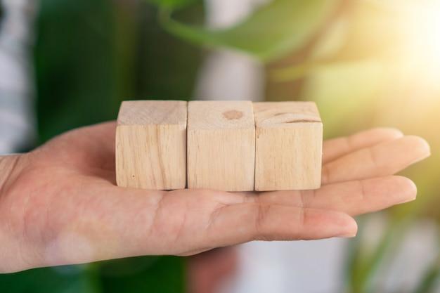 Cubo di legno vuoto su cui puoi mettere il testo o l'icona in mano tenere lo sfondo