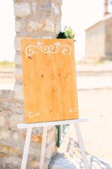 Cavalletto in legno bianco con monogrammi si trova vicino a una colonna di pietra su un supporto