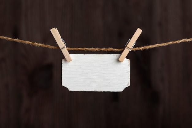 Cartello in legno bianco appeso con mollette sulla corda. targhetta piccola, targa per iscrizione. copia spazio. posto per il testo.