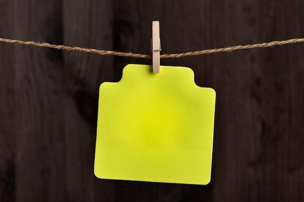 Carta di carta gialla vuota da appendere con molletta sulla corda. copia spazio. posto per il tuo testo. superficie in legno.