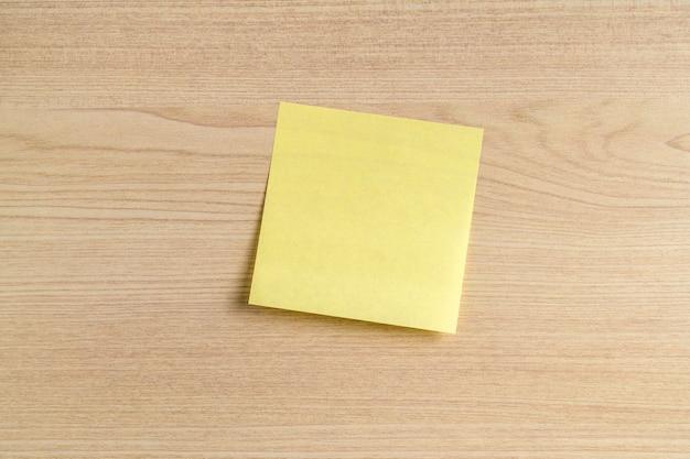 Nota adesiva gialla in bianco, nota postale su sfondo scrivania in legno. copia spazio, mockup