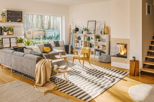 Coperta gettata sul divano ad angolo grigio nell'interno bianco del soggiorno con piante fresche, moquette, camino e poster semplici