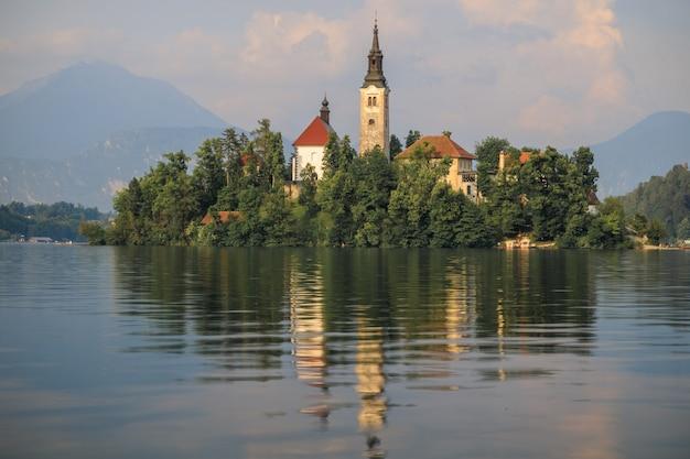 Bled lago slovenia chiesa cattolica sull'isola riflessa nell'acqua calma e pace