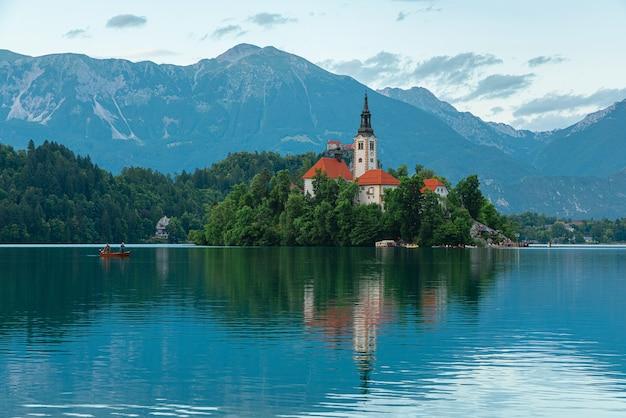 Lago di bled vista dell'isola con la chiesa dell'assunzione di maria sul bellissimo lago con barca nelle alpi giulie, slovenia