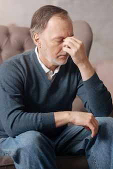 Mal di testa cieco. chiuda in su dell'uomo anziano che ha un terribile mal di testa e tocca il ponte nasale con le dita.