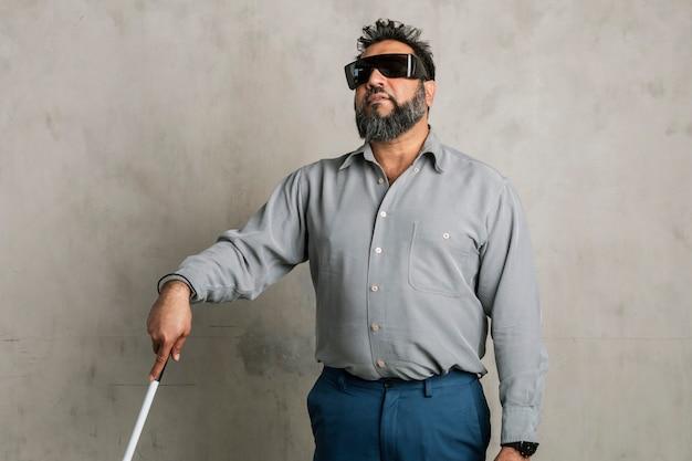 Uomo indiano cieco che indossa occhiali neri e usa un bastone bianco