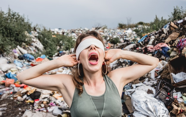 Una volontaria bendata urla dall'impotenza in una discarica di immondizia di plastica. giornata della terra ed ecologia.