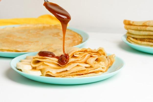 Frittelle blini con caramello, gocciolante su un primo piano di levitazione cucchiaio su un piatto blu su sfondo chiaro