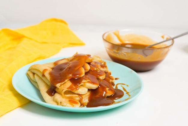 Frittelle di blini con caramello, gocciolante su un primo piano di levitazione del cucchiaio su un piatto blu