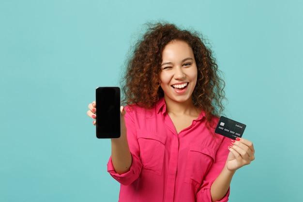 La ragazza africana lampeggiante in abiti casual tiene il telefono cellulare con la carta di credito dello schermo vuoto vuoto isolata su sfondo blu turchese. concetto di stile di vita di emozioni sincere della gente. mock up copia spazio.