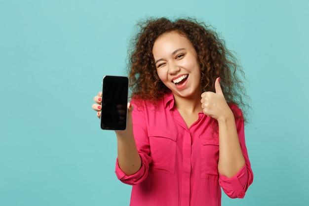 Ragazza africana lampeggiante in abiti casual che mostra pollice in su tenere il telefono cellulare con schermo vuoto vuoto isolato su sfondo blu turchese. concetto di stile di vita di emozioni sincere della gente. mock up copia spazio.