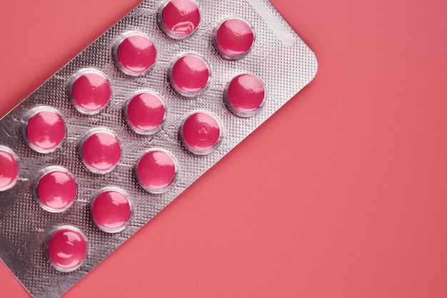Blister pillole rosa vicino isolato su sfondo rosa con copia spazio. medicina digestiva