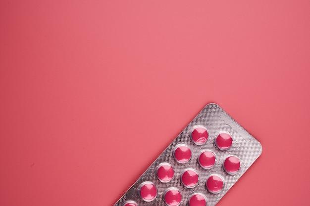 Blister rosa pillole close up isolato su rosa con copia spazio.