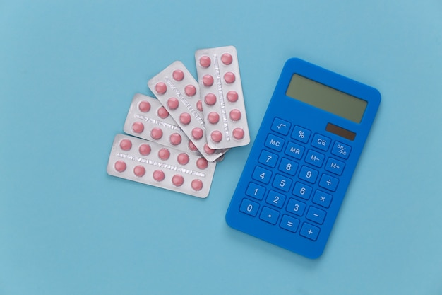 Blister di pillole e calcolatrice su sfondo blu. vista dall'alto