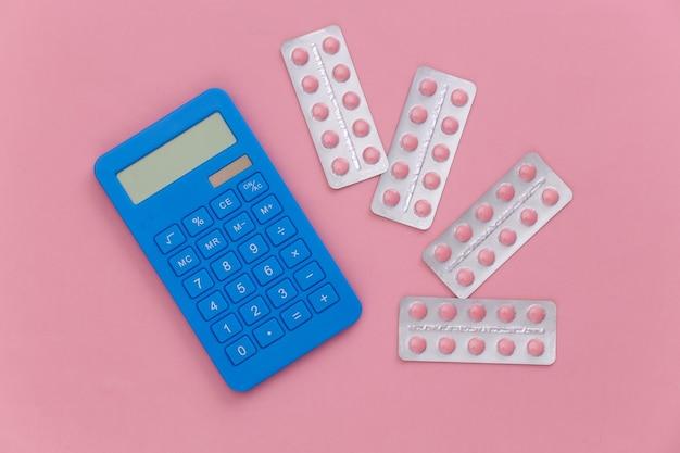 Blister di pillole e calcolatrice su uno sfondo rosa. vista dall'alto