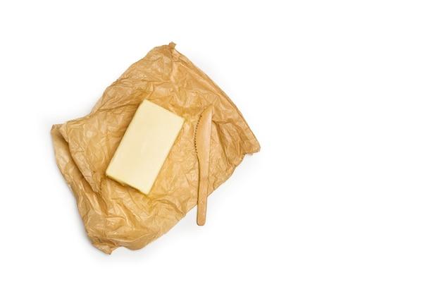 Un blocco di burro su carta marrone rugosa e
