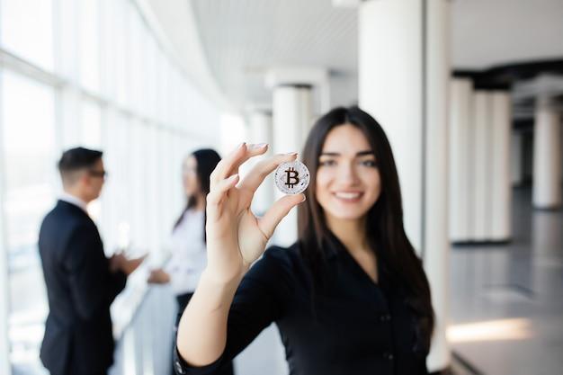 Blockchain e concetto di investimento. leader della donna di affari che tiene bitcoin davanti a discutere la squadra in ufficio.