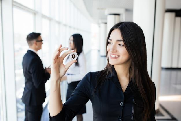 Blockchain e concetto di investimento. leader della donna di affari che tiene bitcoin davanti al suo team di discussione in ufficio.