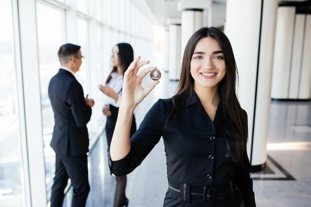 Blockchain e concetto di investimento. leader della donna di affari che tiene litecoin davanti alla sua squadra con le mani alzate sull'ufficio.