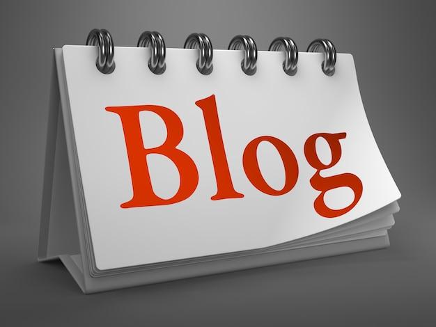 Blog - testo rosso sul calendario desktop bianco isolato su sfondo grigio.