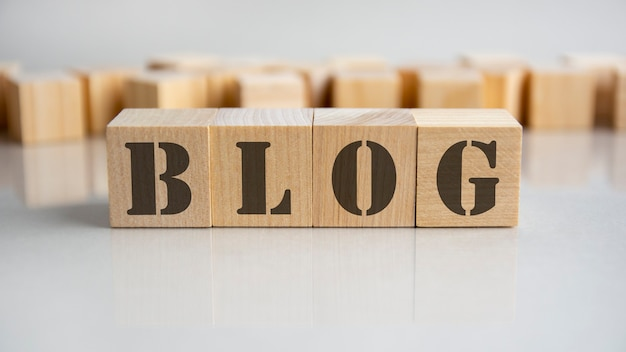 La parola del blog è fatta di blocchi di legno che giacciono sul tavolo grigio, concetto di business