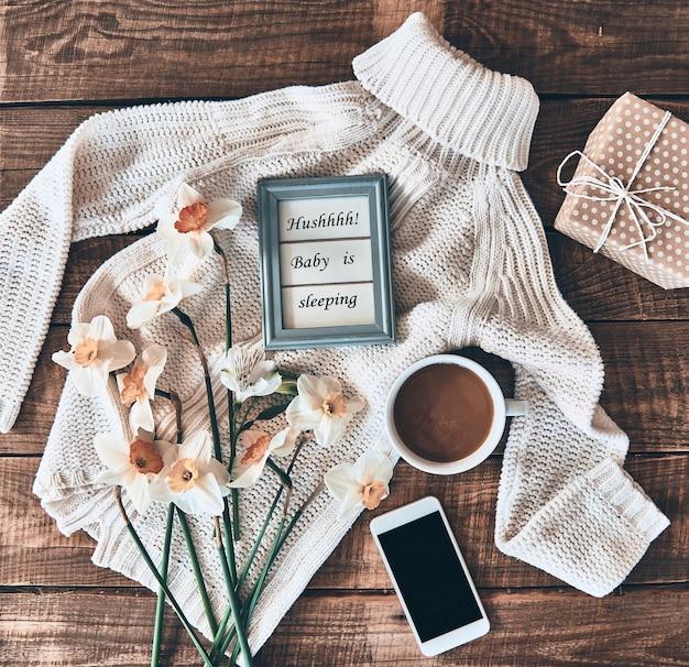 Concetto di blogger. inquadratura dall'alto di maglione, fiori, tazza di caffè, confezione regalo, smartphone