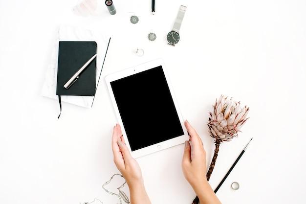 Area di lavoro di blogger o freelance con tablet schermo vuoto, fiore protea, notebook, orologi e accessori femminili su sfondo bianco. scrivania da ufficio decorata in stile minimalista con vista dall'alto piatta.