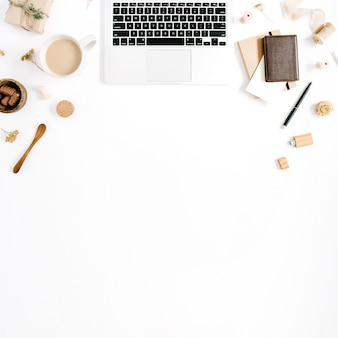 Area di lavoro di blogger o freelance con laptop, tazza da caffè, notebook, dolci e accessori su sfondo bianco. scrivania da ufficio in stile minimalista marrone con vista dall'alto piatta. concetto di blog di bellezza.