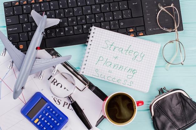 Area di lavoro di blogger o freelance con documenti per notebook tazza di bicchieri di caffè. strategia e pianificazione uguale successo scritto sul taccuino.
