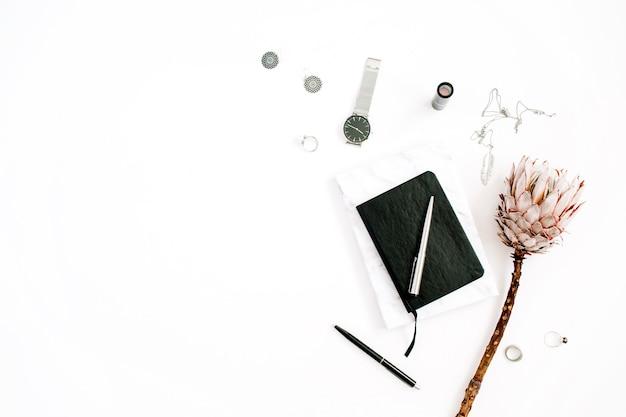 Blogger o spazio di lavoro freelance con fiore protea, notebook e accessori femminili su sfondo bianco. scrivania da ufficio decorata in stile minimalista con vista dall'alto piatta. concetto di blog di bellezza.