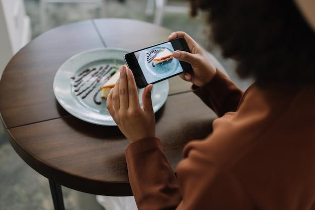 Blogger che tiene smartphone, prendendo foto mobile di gustosa cheesecake con cioccolato, caramello e menta sul piatto