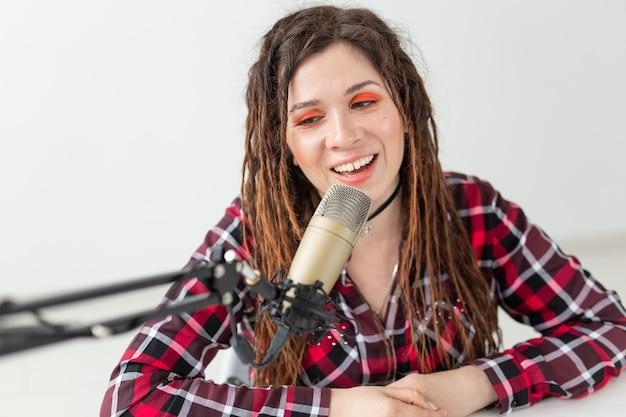 Blogger, conduttore radiofonico e concetto di persone - espressiva ragazza dj moderna con dreadlocks che lavora alla radio.