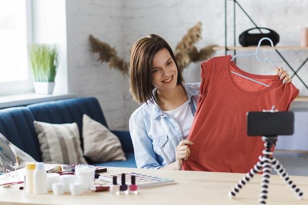 Blogger che mostra vestiti alla macchina fotografica, registrando un video tutorial per il suo blog di moda.