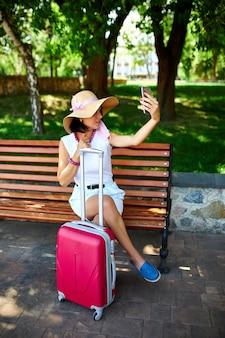 Blogger donna con cappello di paglia e maschera rimossa tiene in testa, nel parco all'aperto con una valigia, scatta selfie, vita durante la pandemia di coronavirus, apertura del viaggio aereo, concetto di viaggio.