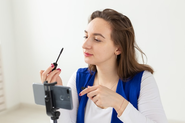 Concetto di blog, trasmissione e cosmetici - un blogger di bellezza o un video blogger la racconta e la mostra