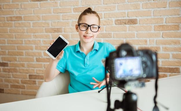 Blogging, videoblog e concetto di persone - videocamera che registra recensione video di blogger adolescente di smartphone in ufficio a casa