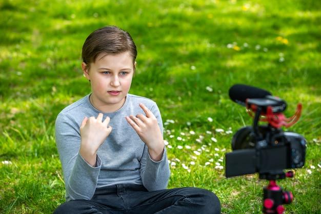 Concetto di blog e vlogging, ragazzo sorridente felice o blogger con video blog di registrazione della fotocamera nella foresta esterna