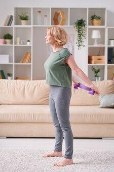 Femmina attiva bionda in t-shirt e leggins in piedi sul pavimento del soggiorno e utilizzando una fascia flessibile mentre si esercita in ambiente domestico