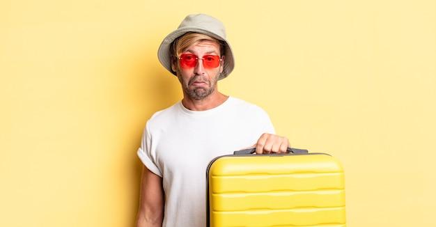 Uomo adulto biondo che si sente triste e piagnucoloso con uno sguardo infelice e piange. concetto di viaggiatore