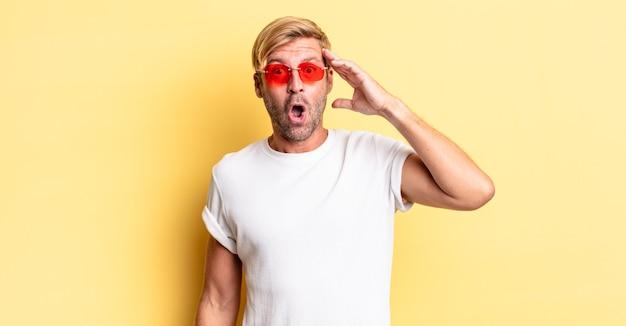 Uomo adulto biondo che sembra felice, stupito e sorpreso e indossa occhiali da sole