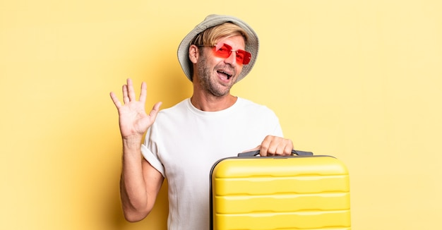 Uomo adulto biondo che sorride felicemente, agitando la mano, accogliendoti e salutandoti. concetto di viaggiatore