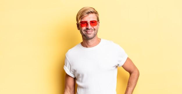 Uomo adulto biondo che sorride felicemente con una mano sull'anca e fiducioso e indossa occhiali da sole