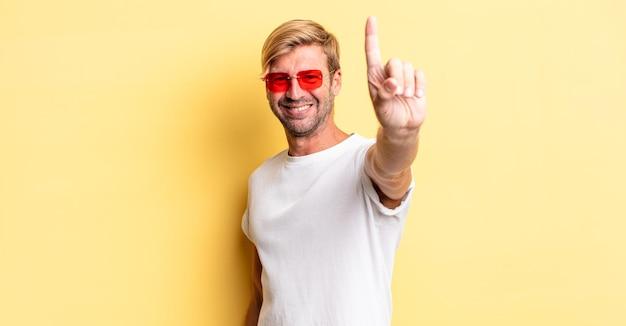 Uomo adulto biondo che sorride con orgoglio e sicurezza facendo il numero uno e indossando occhiali da sole