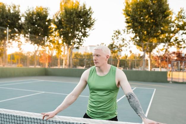 Uomo biondo albino atleta su un campo da tennis
