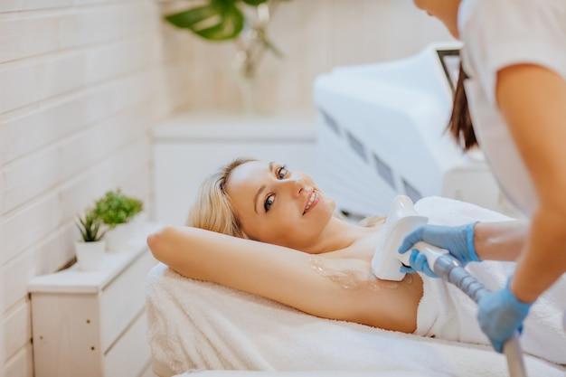 Donna attraente bionda in accappatoio bianco che pone sulla sedia di cosmetologia e riceve la procedura di rimozione dei peli per le braccia.