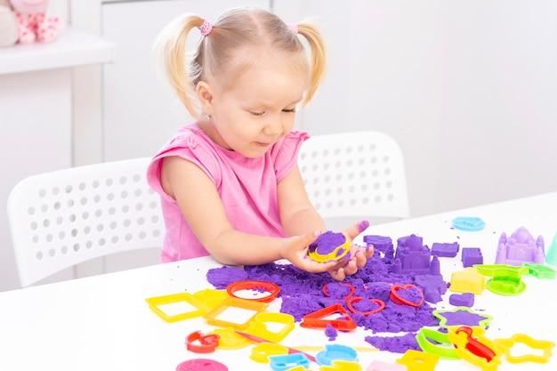 La bella ragazza bionda sorride e gioca con la sabbia viola su un tavolo bianco.