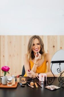 Blogger di bellezza bionda che applica rossetto liquido